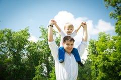 Netter kleiner Junge auf den Schultern seines Vaters gegen Stockfoto