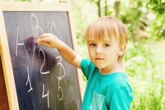 Netter kleiner Junge an an der übender Zählung und Mathe der Tafel im Freien Stockbilder