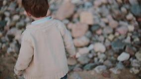 Netter kleiner Junge, der auf dem Sand nahe den Steinen, Verschiebung von einem Fuß zum anderen läuft Männliches draußen gehen stock footage