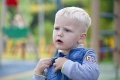 Netter kleiner Junge, der auf dem Spielplatz strandet Stockfotos