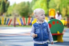 Netter kleiner Junge, der auf dem Spielplatz strandet Lizenzfreies Stockbild
