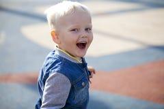 Netter kleiner Junge, der auf dem Spielplatz strandet Stockfotografie