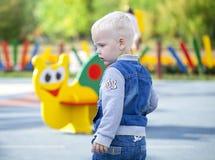 Netter kleiner Junge, der auf dem Spielplatz strandet Lizenzfreie Stockbilder
