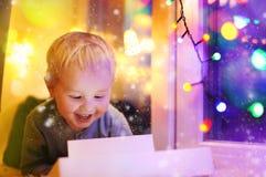 Netter kleiner Junge, der auf einem magischen Weihnachten oder einem Neujahrsgeschenk schaut Stockfoto
