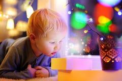 Netter kleiner Junge, der auf einem magischen Weihnachten oder einem Neujahrsgeschenk schaut Stockfotografie