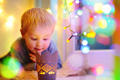 Netter kleiner Junge, der auf einem magischen Weihnachten oder einem Neujahrsgeschenk schaut Lizenzfreies Stockbild