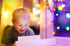 Netter kleiner Junge, der auf einem magischen Weihnachten oder einem Neujahrsgeschenk schaut Lizenzfreie Stockbilder