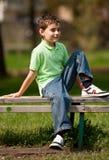 Netter kleiner Junge, der auf einer Bank sitzt Lizenzfreie Stockbilder