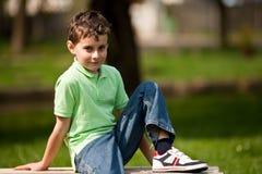 Netter kleiner Junge, der auf einer Bank sitzt Stockfotos