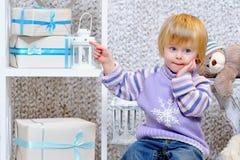 Netter kleiner Junge, der auf Geschenkboxen zeigt Stockfoto