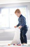 Netter kleiner Junge, der Beutel mit Spielwaren entpackt Lizenzfreie Stockfotos