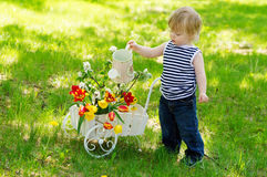 Netter kleiner Junge, der bunte Blumen wässert Stockbild