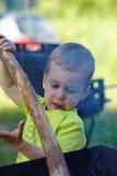 Netter kleiner Junge, der das Anzünden, zum eines Feuers unter Verwendung eines Stockes zu beginnen sorgfältig sich konzentriert  Stockfotografie