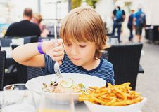 Netter kleiner Junge, der das Mittagessen isst lizenzfreie stockbilder