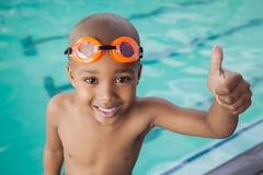 Netter kleiner Junge, der Daumen am Pool aufgibt Stockbild