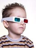 Netter kleiner Junge, der in den Gläsern 3D sitzt Stockbild