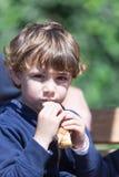 Netter kleiner Junge, der den Pfannkuchen im Freien isst Lizenzfreie Stockfotografie