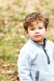 Netter kleiner Junge, der die Kamera betrachtet Stockbilder