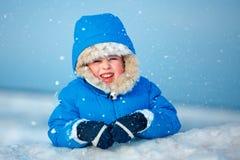 Netter kleiner Junge, der draußen auf Winterstrand spielt lizenzfreies stockbild