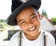 Netter kleiner Junge, der draußen mit Hut lächelt Stockbilder