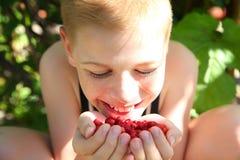Netter kleiner Junge, der eine Erdbeere isst Lizenzfreies Stockfoto