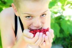 Netter kleiner Junge, der eine Erdbeere isst Stockbild