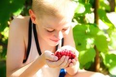 Netter kleiner Junge, der eine Erdbeere isst Stockfotografie