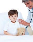 Netter kleiner Junge, der eine medizinische Überprüfung bedient Stockbild
