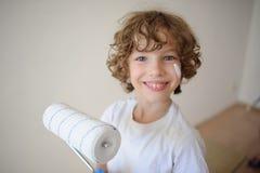 Netter kleiner Junge, der eine Rolle für das Malen hält Lizenzfreies Stockbild
