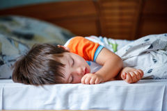 Netter kleiner Junge, der in einem Bett schläft Stockfotografie