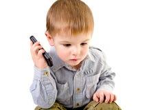 Netter kleiner Junge, der an einem Handy spricht Lizenzfreie Stockfotografie