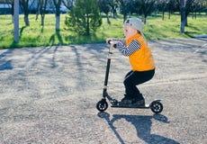 Netter kleiner Junge, der einen Roller reitet Stockfotografie