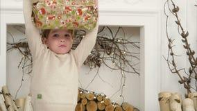 Netter kleiner Junge, der eingewickeltes Weihnachtsgeschenk überprüft und glücklich mit ihm tanzt stock video