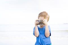 Netter kleiner Junge, der einige Fotos am Strand, Thailand macht Stockbild