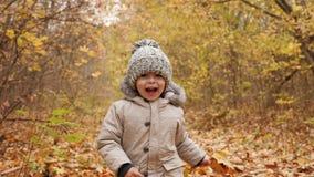 Netter kleiner Junge, der Energie- entlang den Herbstparkweg läuft stock video
