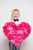 Netter kleiner Junge in der Fliege, die großes Herz von den Papierblumen hält Stockbilder