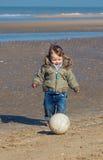 Netter kleiner Junge, der Fußball spielt Lizenzfreie Stockfotos