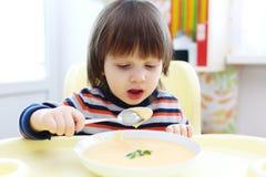 Netter kleiner Junge, der Gemüsesahnesuppe isst Stockfoto