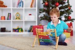 Netter kleiner Junge, der Geschenke mit hölzernem Abakus zählt Lizenzfreies Stockfoto