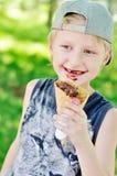Netter kleiner Junge, der geschmackvolle Eiscreme isst Stockfotos