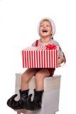 Netter kleiner Junge, der großes anwesendes und Lachen hält Weihnachtsniederlassung und -glocken Lizenzfreie Stockbilder