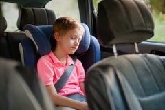 Netter kleiner Junge, der im Autositz schläft stockbilder