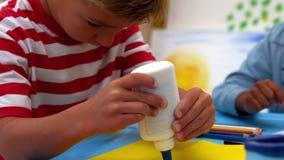Netter kleiner Junge, der Kleber im Klassenzimmer verwendet stock footage