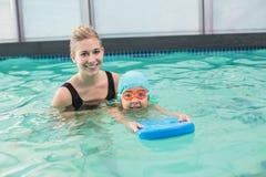 Netter kleiner Junge, der lernt, mit Trainer zu schwimmen lizenzfreie stockfotos