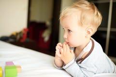 Netter kleiner Junge, der mit Blöcken spielt Stockbild