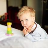Netter kleiner Junge, der mit Blöcken spielt Stockfoto