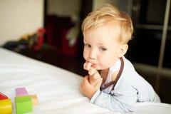 Netter kleiner Junge, der mit Blöcken spielt Stockfotografie