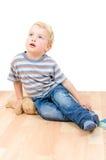 Netter kleiner Junge, der mit dem Teddybären und Buch lokalisiert sitzt Lizenzfreies Stockbild