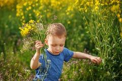 Netter kleiner Junge, der mit einem Blumenstrauß von Blumen auf einem Gelb mich laufen lässt Lizenzfreies Stockfoto