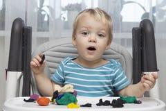 Netter kleiner Junge, der mit Lehmteig spielt oder Knetmasse-, Bildungs- und Kindertagesstättenkonzept modelliert stockbilder